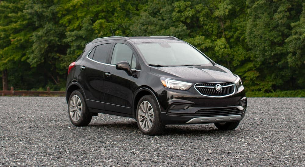 A popular used luxury SUV, a black 2020 Buick Encore, is parked on gravel in front of trees.