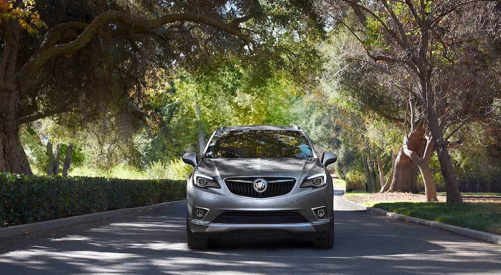 A gray 2020 Buick Envision is shown from the front driving on a tree-lined road.