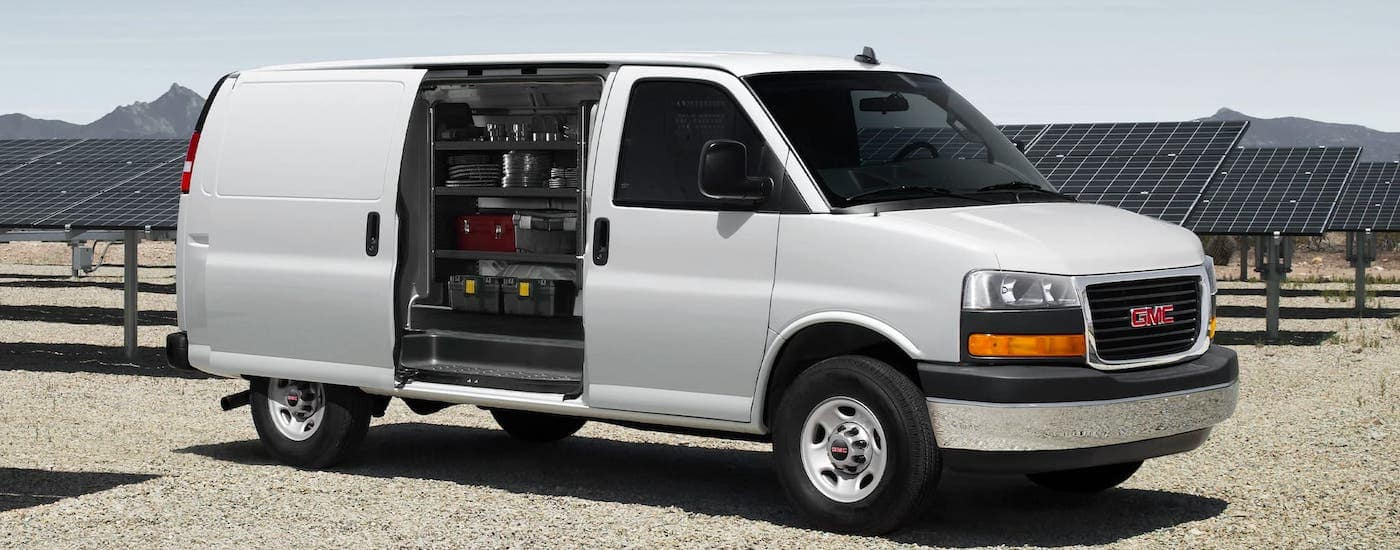 A white 2021 GMC Savana cargo van is parked in front of solar panels while the side door is open and showing shelves and tools.