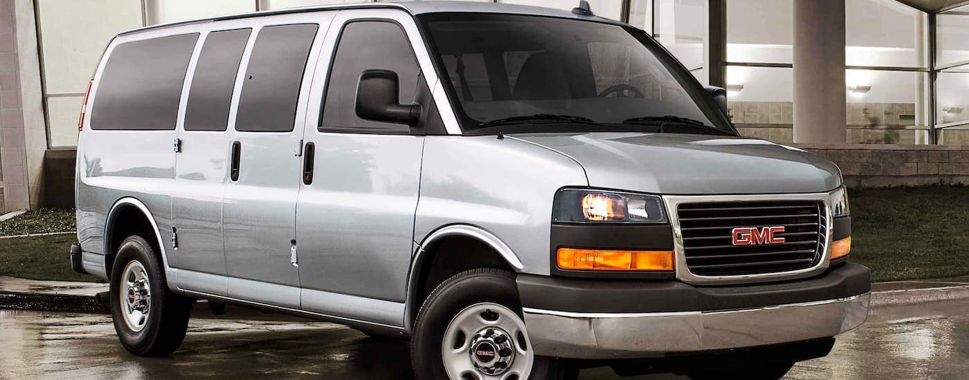 A silver 2021 GMC Commercial Savana passenger van is parked in front of a glass building.