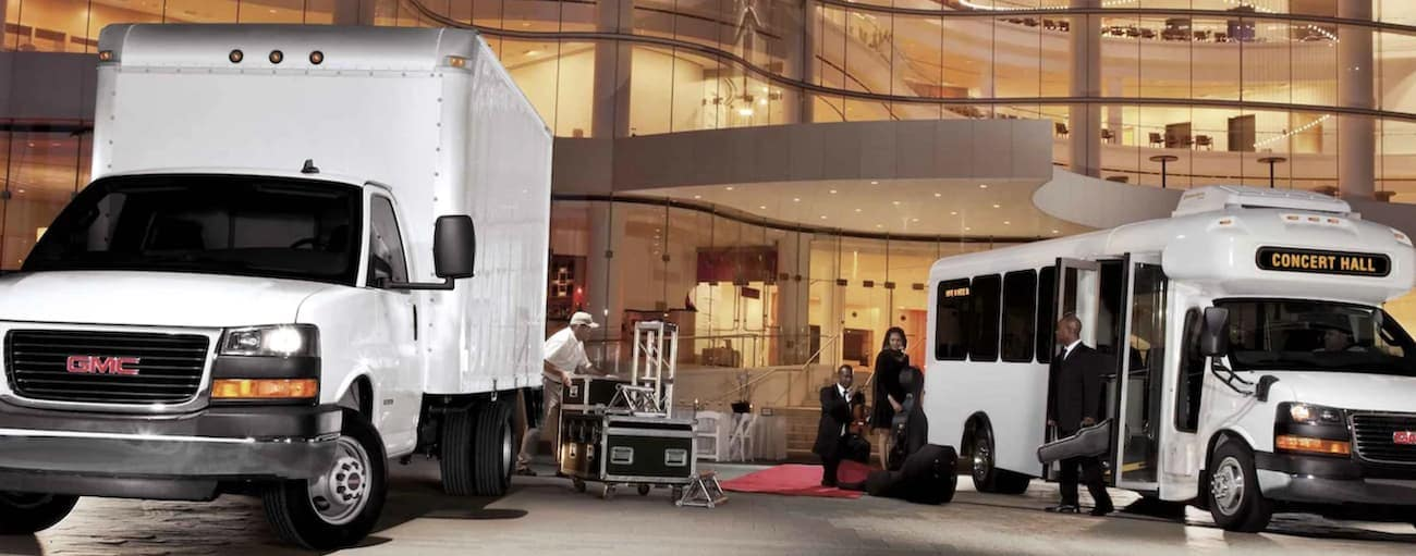 Two 2021 GMC Commercial Vehicles, both white Savana Cutaways, are outside a building at night with music equipment.