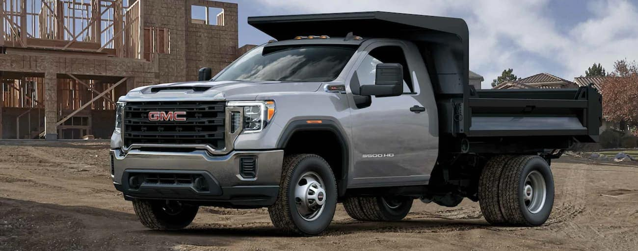 A grey 2021 GMC Sierra 3500 Chassis Cab is parked in front of a home under construction.