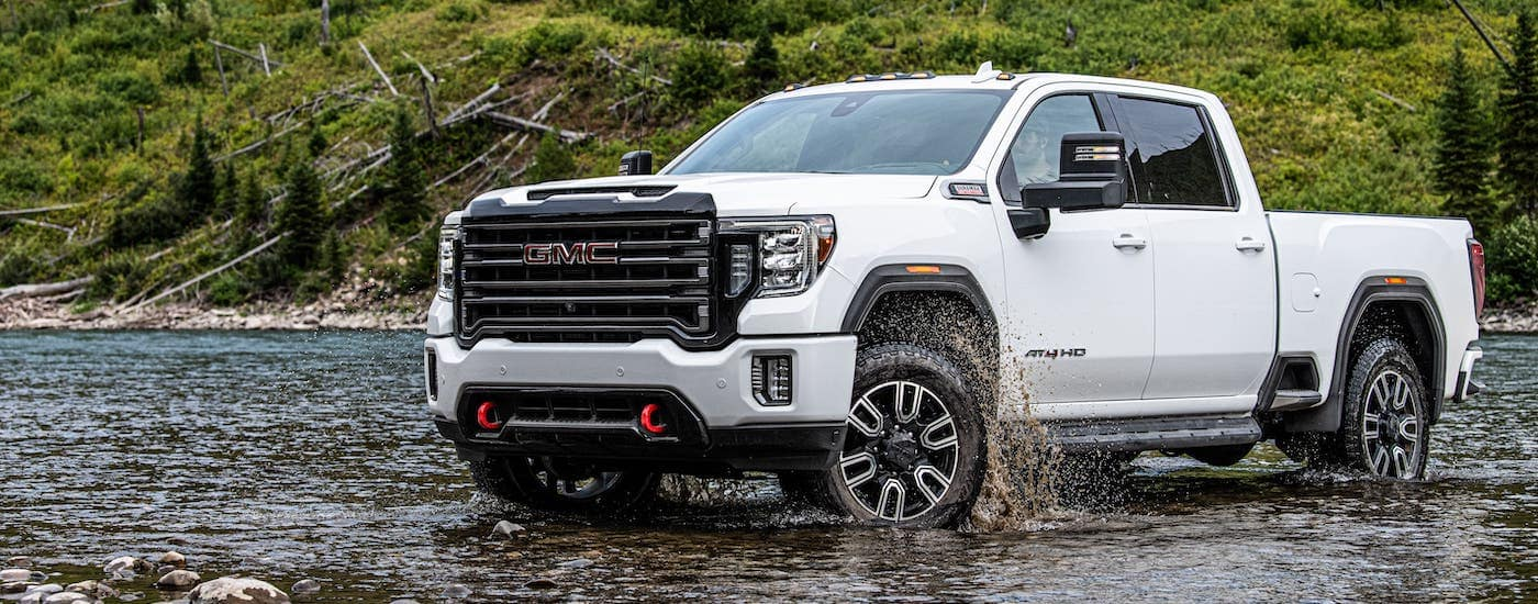 A white 2021 GMC Sierra 2500HD AT4 is crossing a river.