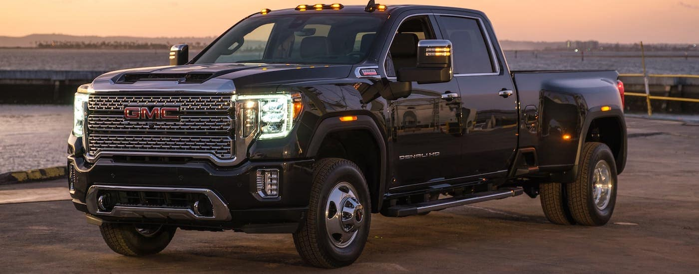 One of the larger 2021 GMC Heavy duty trucks, a black 2021 GMC Sierra 3500HD Denali is parked on a pier at sunset.