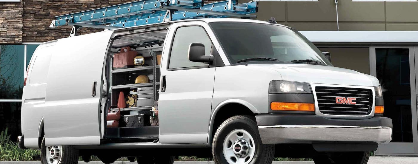 A silver 2021 GMC work van Savana Cargo has a ladder on the roof and the side door open showing tools.