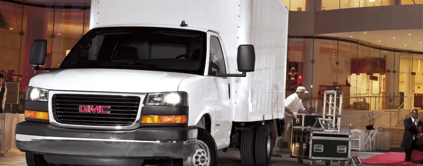 A white 2021 GMC Savana Cutaway box truck is parked in front of a loading dock.