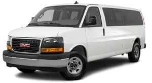 A white 2021 GMC Savana passenger van is angled left.