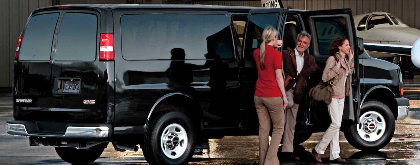 People are getting out of a black 2021 GMC Savana passenger van.