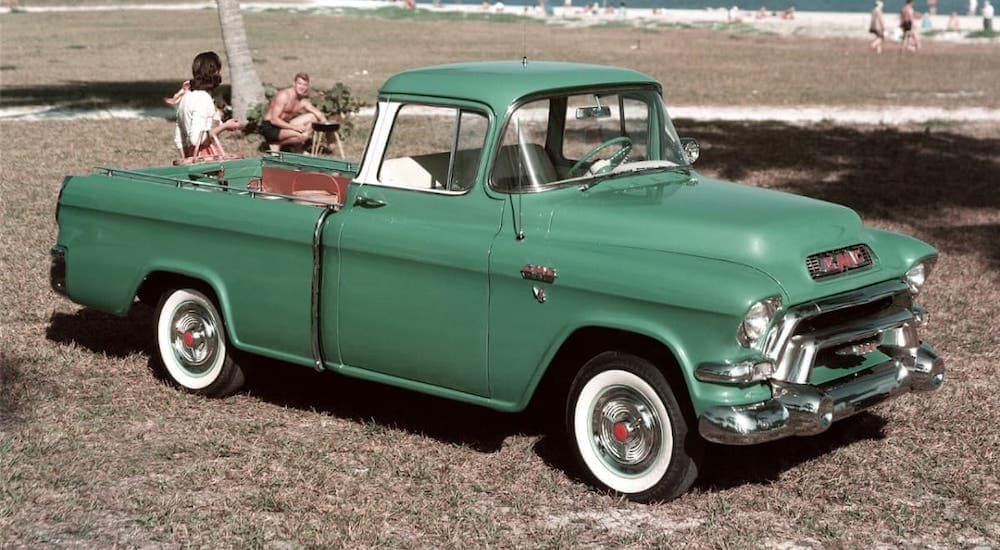 A classic photo shows a green 1955 GMC Suburban Pickup truck parked at a beach.
