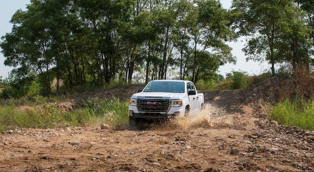 A white 2021 GMC Canyon AT4 from an Atlanta truck dealer is kicking up dirt on a trail.
