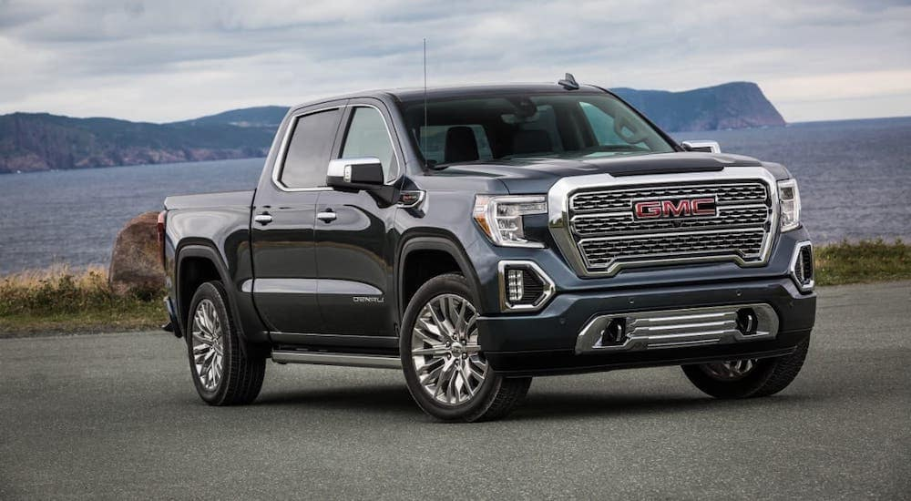 A gray 2021 GMC Sierra 1500 Denali is parked in front of a lake.