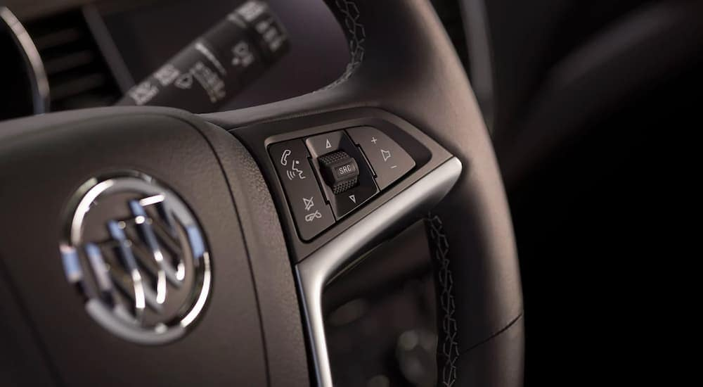 A close up shows the steering wheel controls on a 2021 Buick Encore.