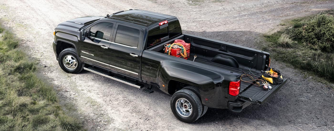 A black 2015 GMC Sierra Denali 3500 HD is shown from a high angle parked on a dirt path.