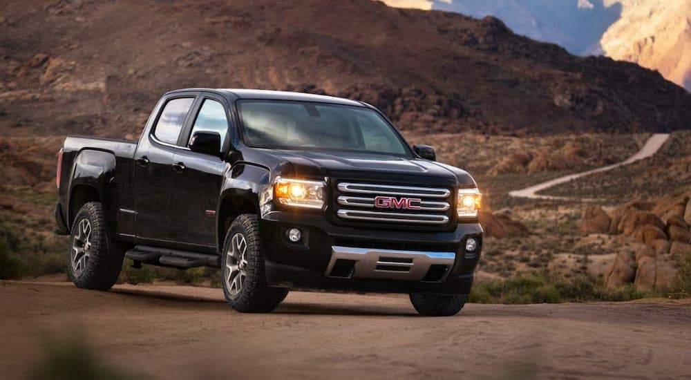 A black 2017 GMC Canyon is parked in front of mountains.