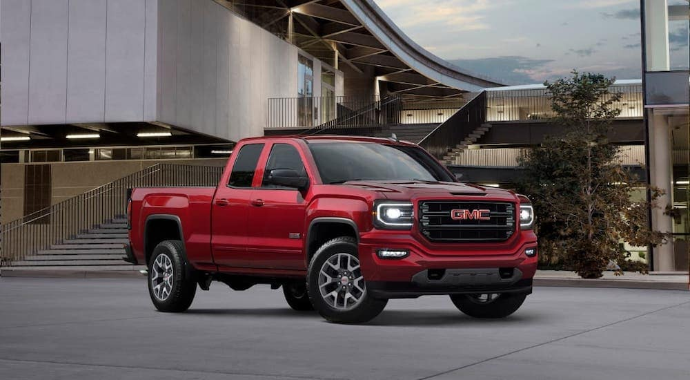 A popular used truck in Atlanta, a red 2018 GMC Sierra 1500 All Terrain, is parked in front of a building.