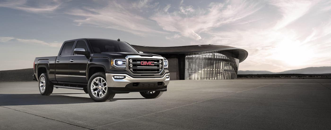 A black 2018 GMC Sierra SLT is parked in front of a modern building.
