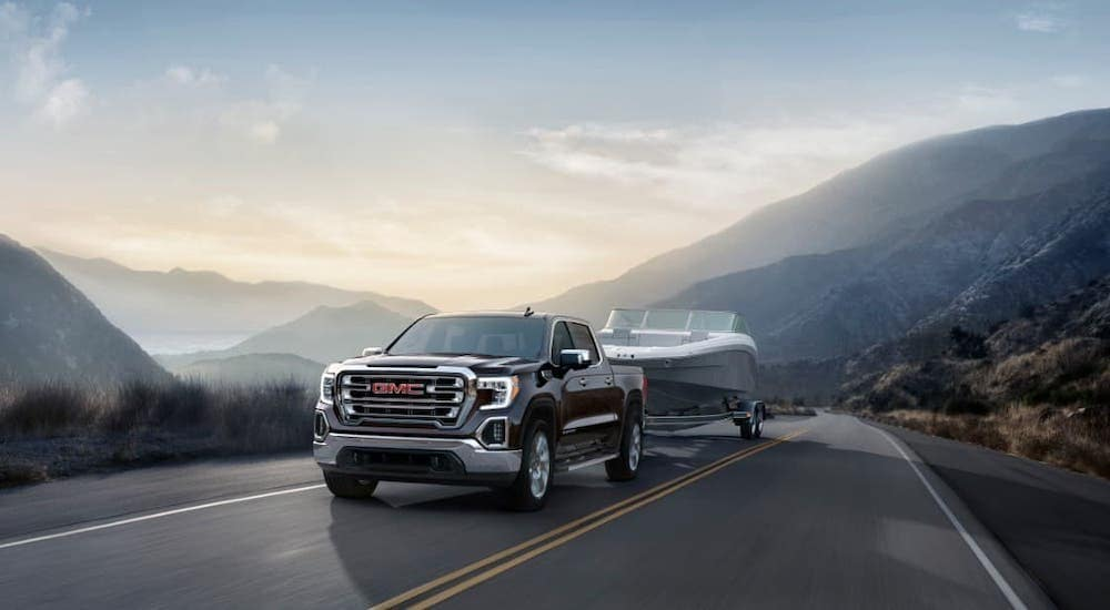 A black 2019 GMC Sierra 1500 is towing a boat in front of mountains.