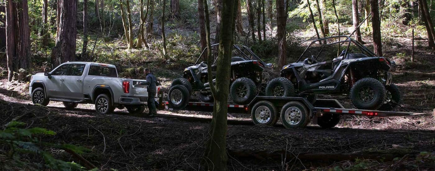 A white 2021 GMC Sierra 2500 HD AT4 is shown towing ATVs in the woods.