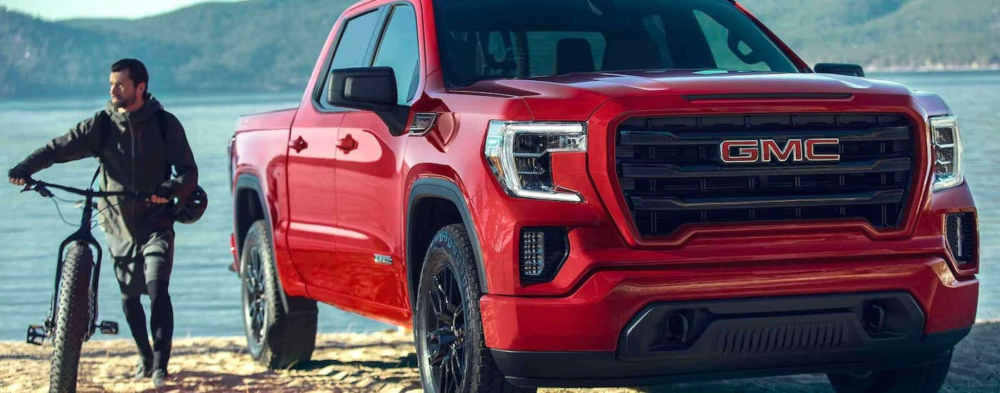 A red 2021 GMC Sierra 1500 is parked on a lake shore with a man walking a bike next to it.