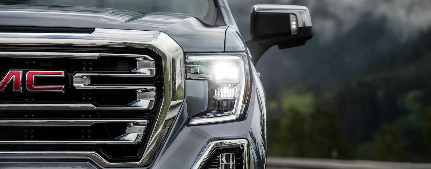 A close up is shown of the grille and drivers side headlight on a gray 2021 GMC Sierra 1500.