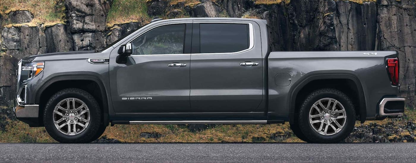 A gray 2021 GMC Sierra 1500 is shown from the side with a rock face in the background.