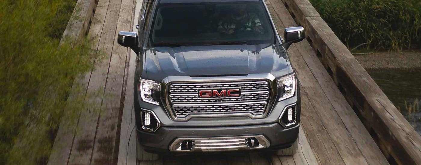 A dark grey 2021 GMC Sierra 1500 is shown from a high angle driving over a wooden bridge.
