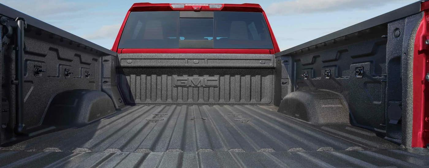 A close up is shown of the bed and tailgate on a red 2021 GMC Sierra 2500 HD.