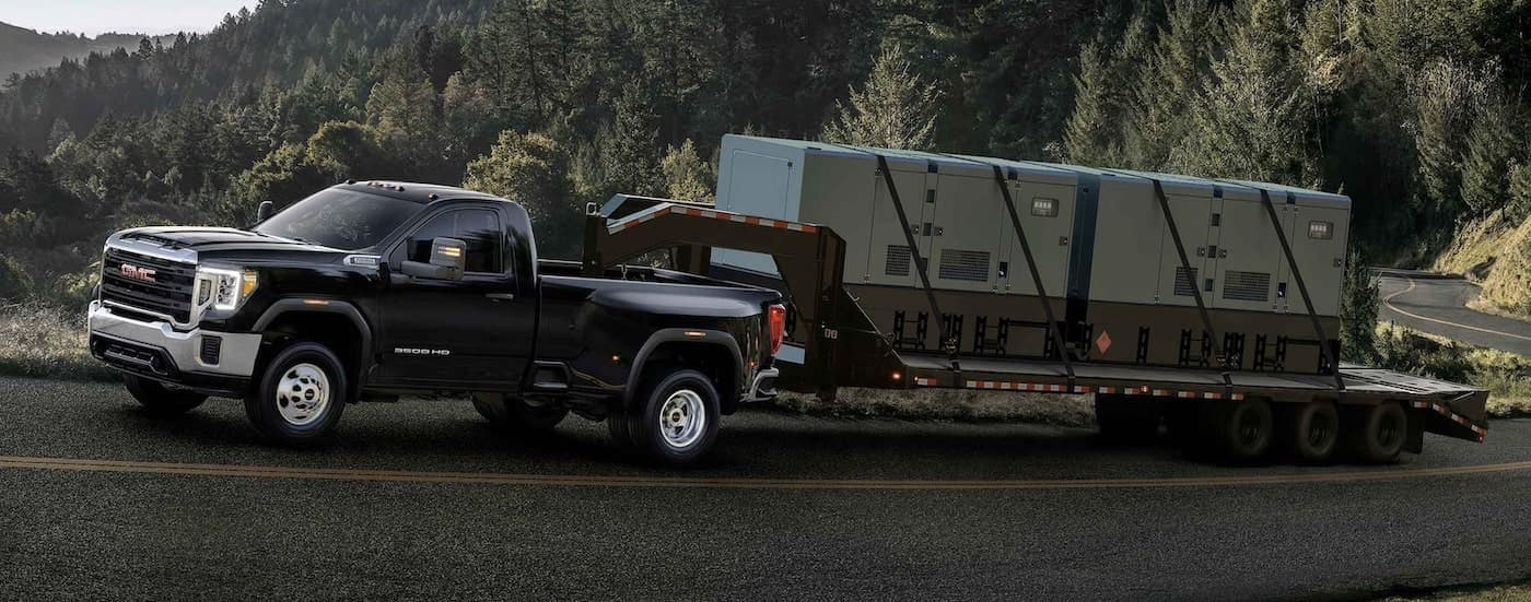 A black 2021 GMC Sierra 2500 HD is towing a gooseneck trailer up a tree-lined road.