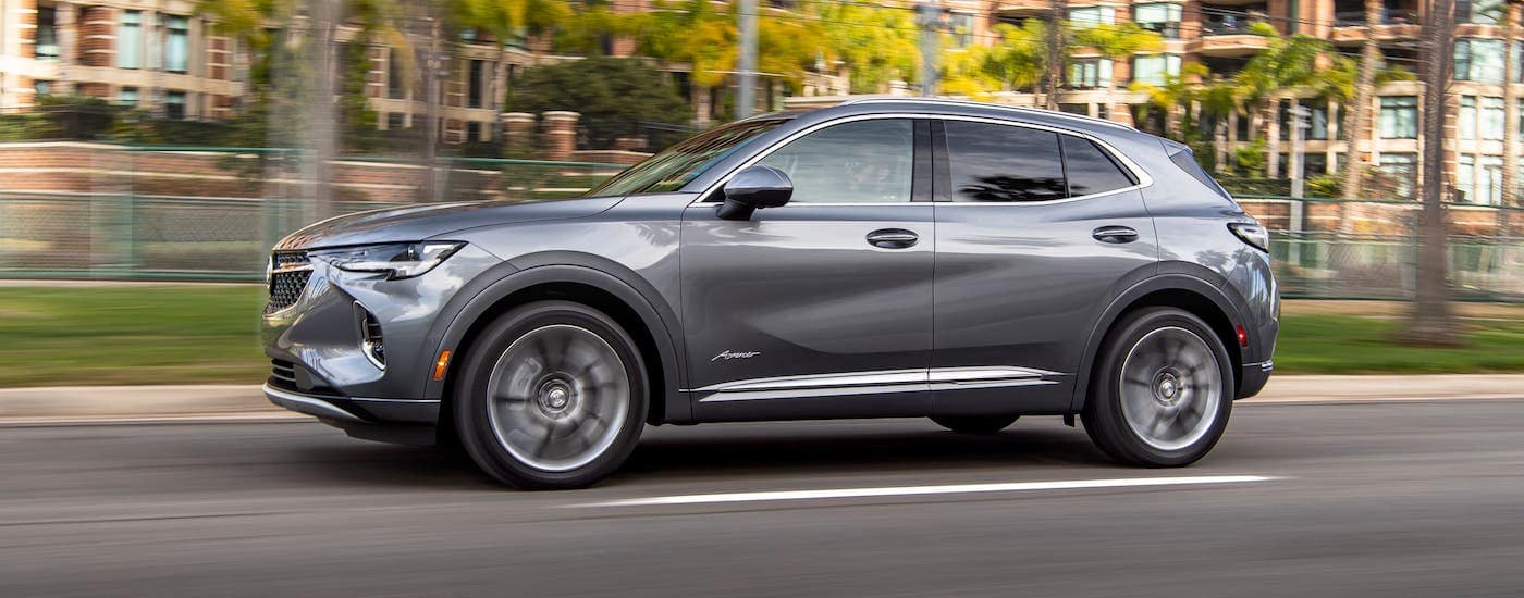 A gray 2021 Buick Envision Avenir is driving on a road past blurry trees and buildings.