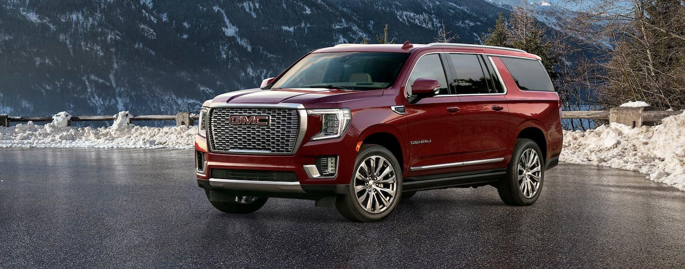 A dark red 2021 GMC Yukon XL Denali is parked in front of a snowy mountain.