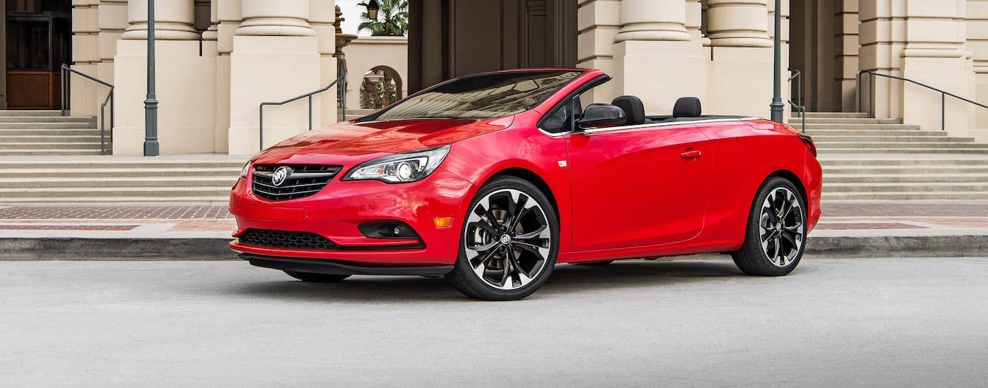 A red 2019 Buick Cascada convertible is parked in front of a building with columns and stairs.