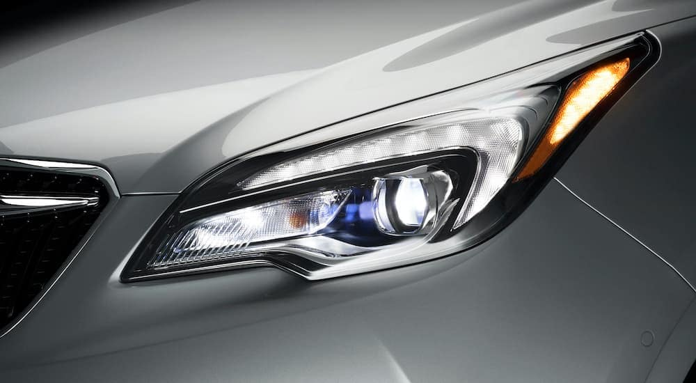A close up shows the driver side headlight of a silver 2019 Buick Envision.