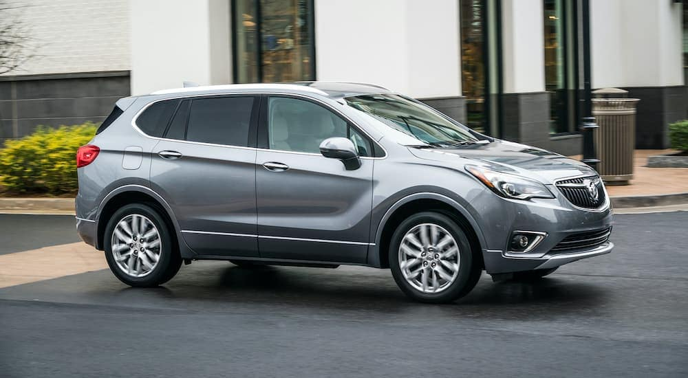 A popular used Buick in Atlanta, a gray 2019 Buick Envision, is shown from the side driving past a blurred building.