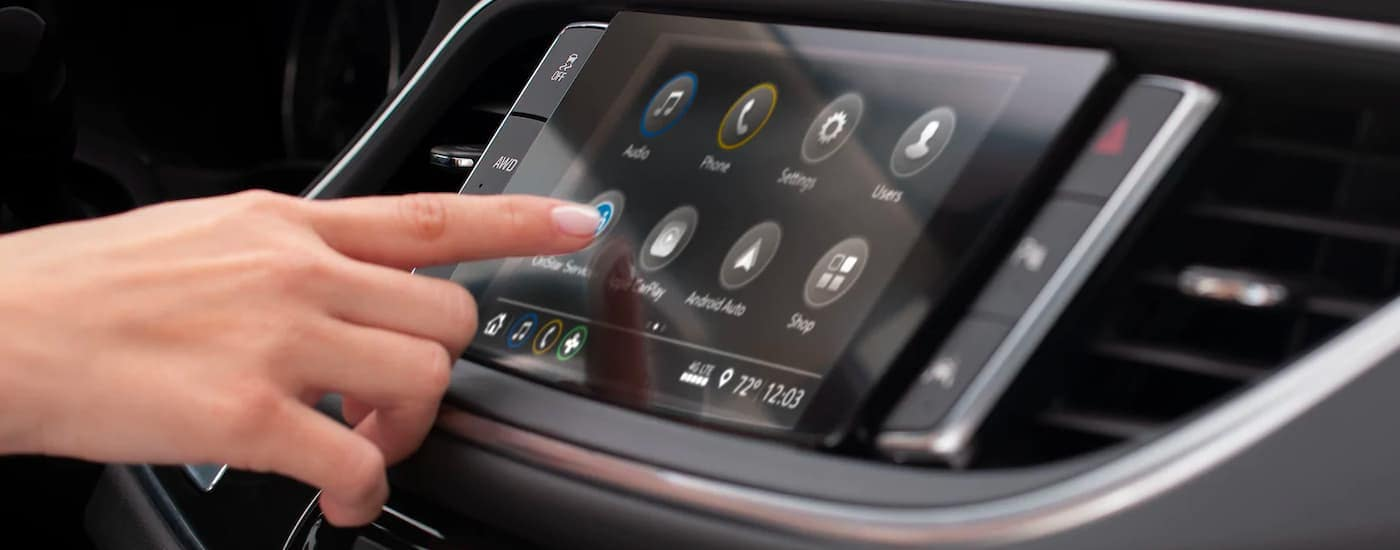 A close up shows a hand making a selection on the infotainment system of a 2021 Buick Enclave.