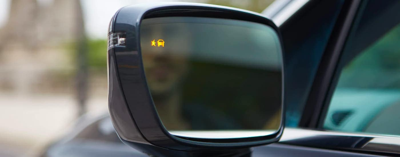 A close up shows the illuminated blind spot indicator on the side mirror of a dark grey 2021 Buick Enclave.