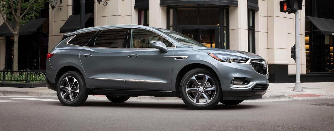 A silver 2021 Buick Enclave is shown from the side driving through an intersection.