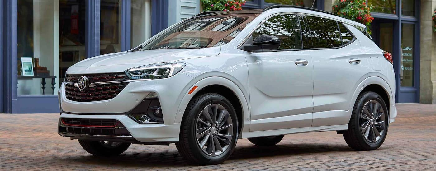 A white 2021 Buick Encore GX is shown from the side parked in front of a shop.