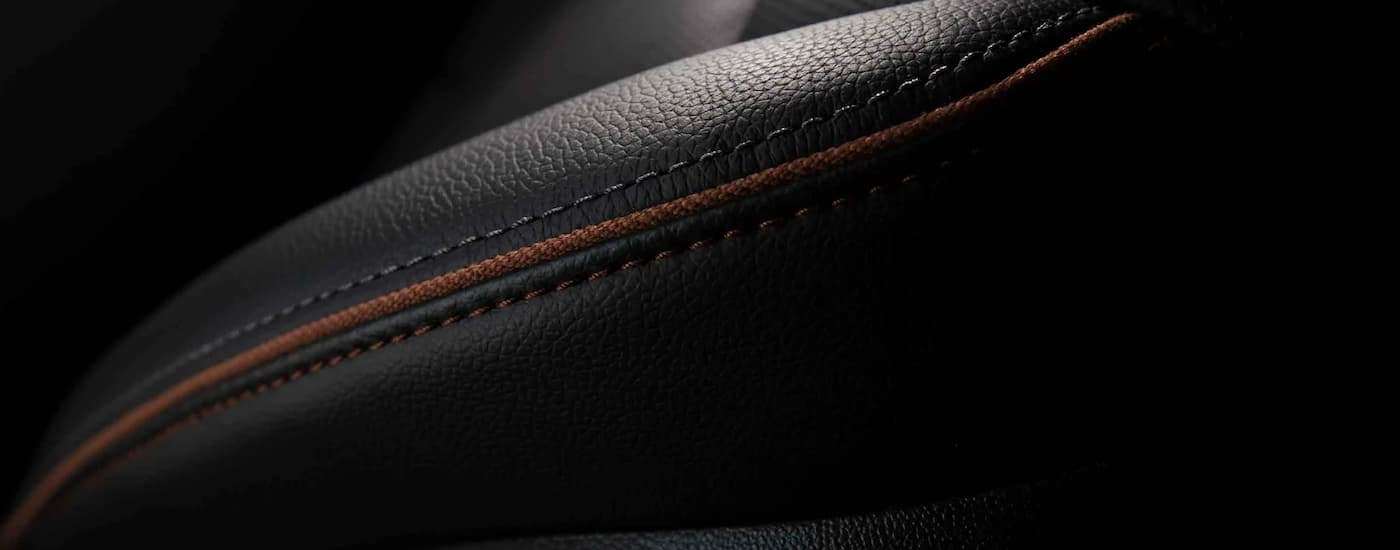 A close up shows the black leather and orange stitching on 2021 GMC Acadia AT4.