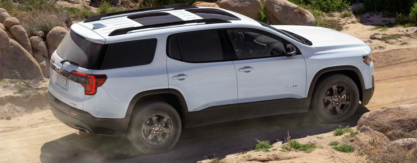 A white 2021 GMC Acadia AT4 is off-roading on a dirt path with rocks in the background.