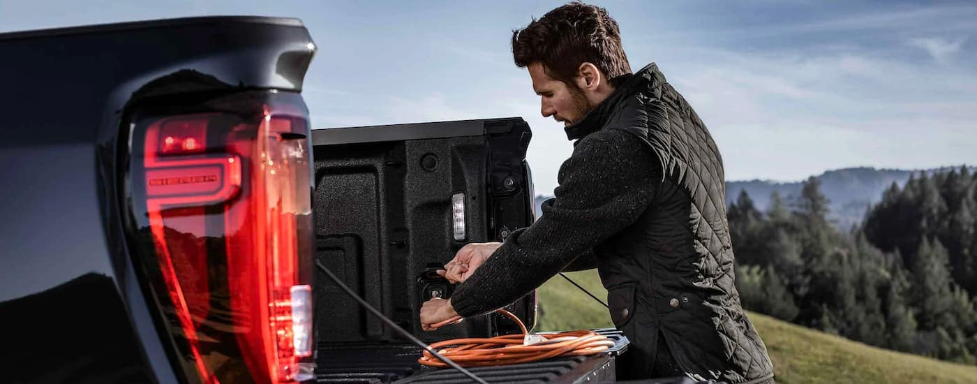 A man is shown plugging in an extension chord into the bed of a black 2021 GMC Sierra 3500HD.