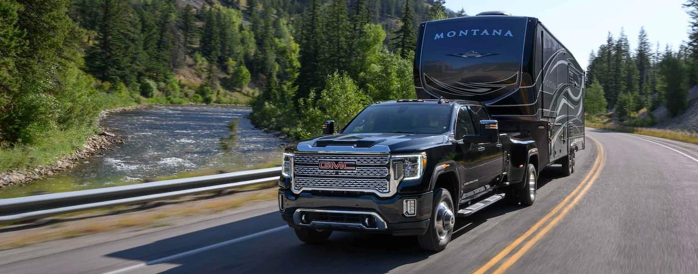 A black 2021 GMC Sierra 3500HD is towing a large trailer past evergreen tress and mountains.