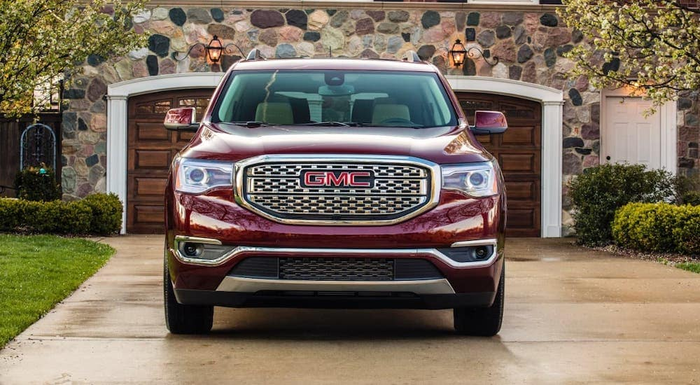 A red 2021 GMC Acadia Denali is shown from the front in front of a stone garage.
