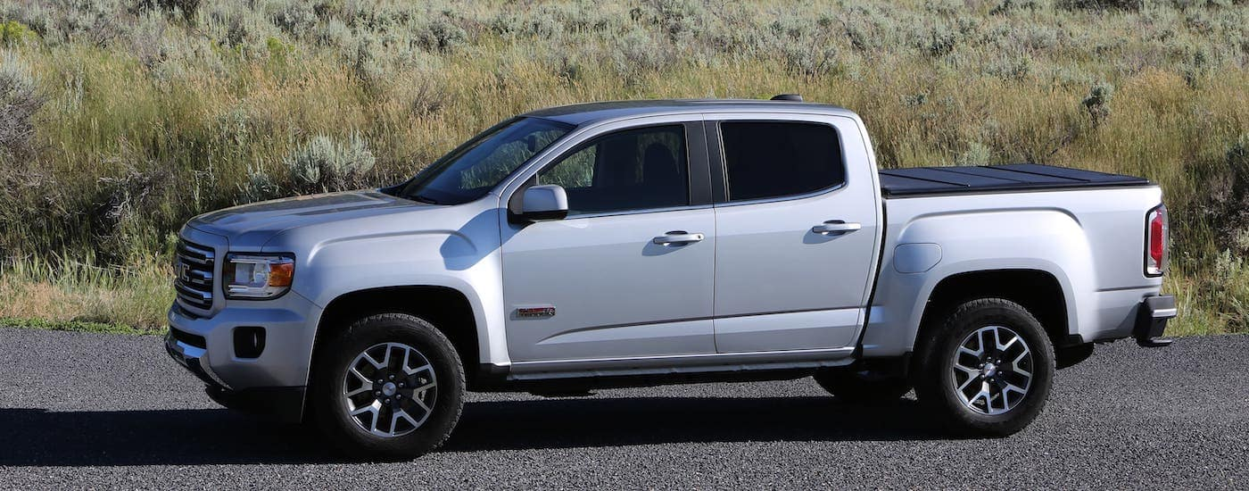 A silver 2021 GMC Canyon is shown from the side parked in front of tall grass.