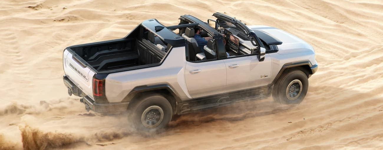 A silver 2022 GMC Hummer EV Truck with no roof is shown from a high angle off-roading on desert sand.