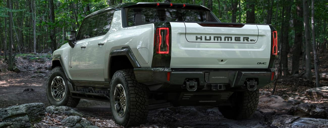A white 2022 GMC Hummer EV Truck is shown from the rear off-roading in the woods.