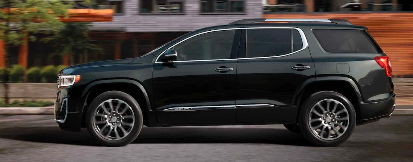 A black 2021 GMC Acadia Denali is shown from the side driving on a city street.