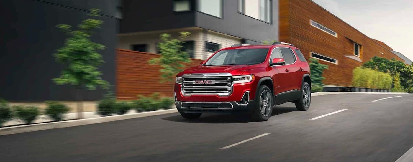 A red 2021 GMC Acadia is driving on a city street as part of the 2021 GMC Acadia vs 2021 Kia Telluride comparison.