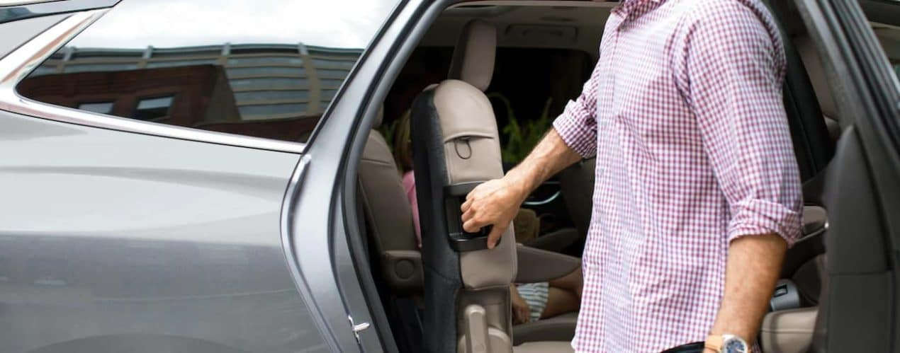 A man is folding the rear seat down through an open door in a 2021 Buick Enclave.