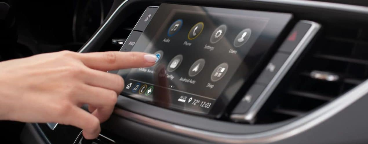 A hand is using the touch screen in a 2021 Buick Enclave after it won the 2021 Buick Enclave vs 2022 Nissan Pathfinder comparison.