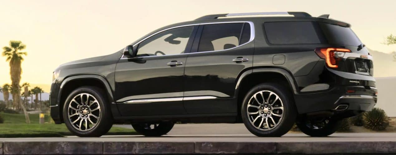 A black 2021 GMC Acadia is shown from the side at sunset.